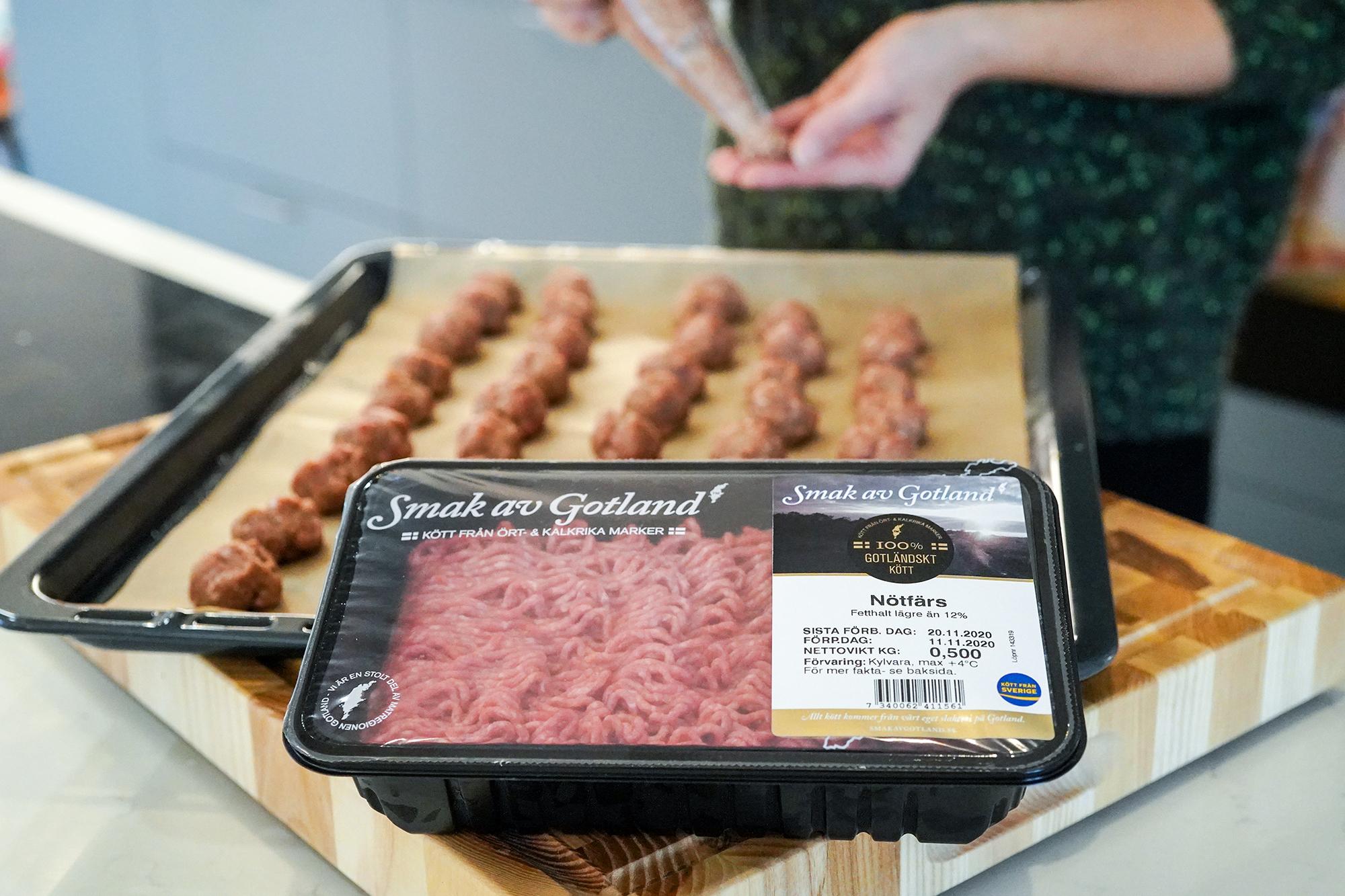Person gör köttbullar i bakgrunden av en förpackning av nötfärs
