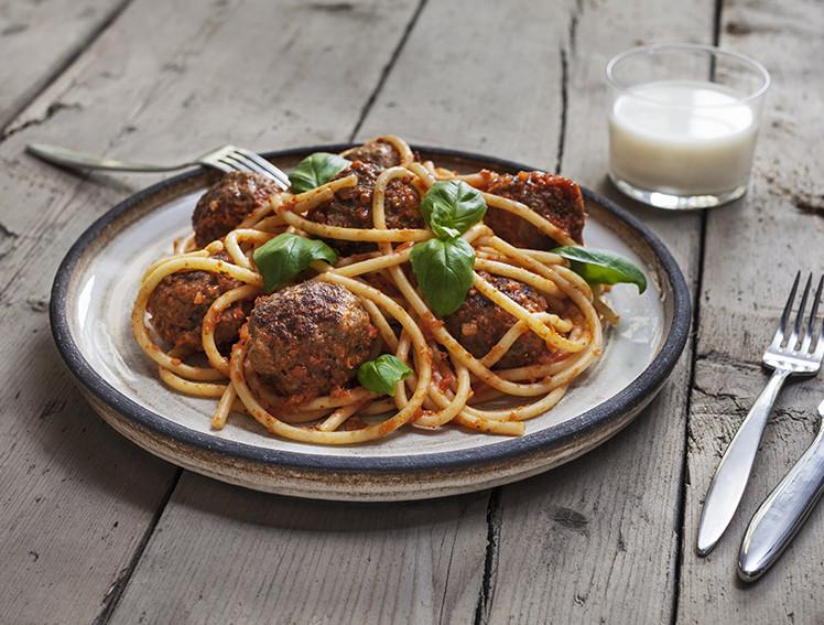 En tallrik serverad med tjock spagetti och stora köttbullar toppad med basilika med ett glas mjölk till