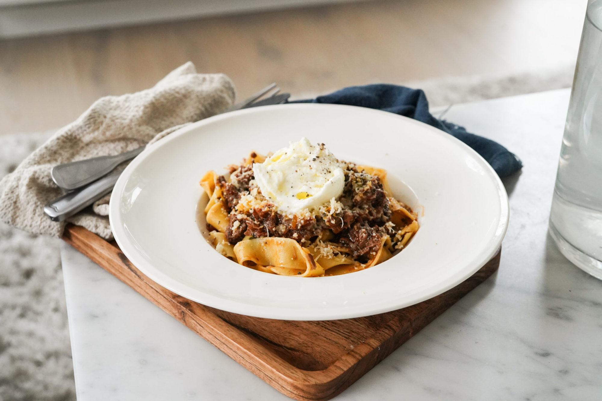En tallrik med en pasta toppad med mozzarella och olivolja serverad på en bricka