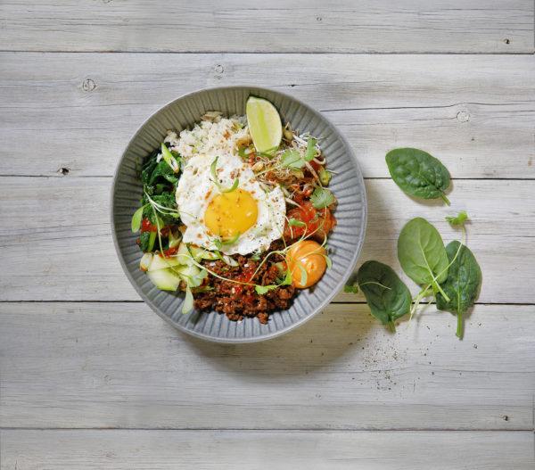 En skål med grönsaker, kött, örter och lime toppat med ett stekt ägg