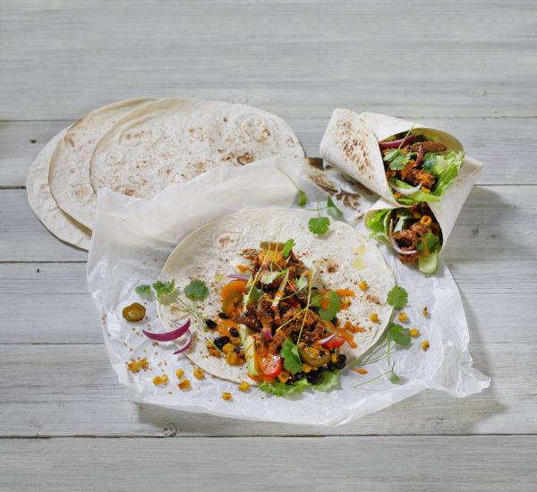 Tacobröd med kött grönskaer örter och andra färgsprakande tillbehör