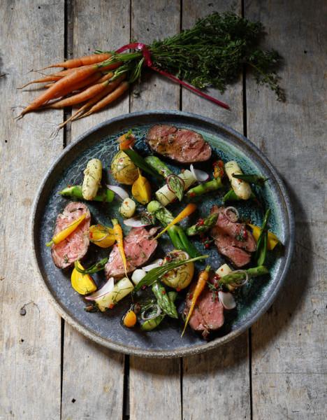 En tallrik med skivor av kött och grönsaker
